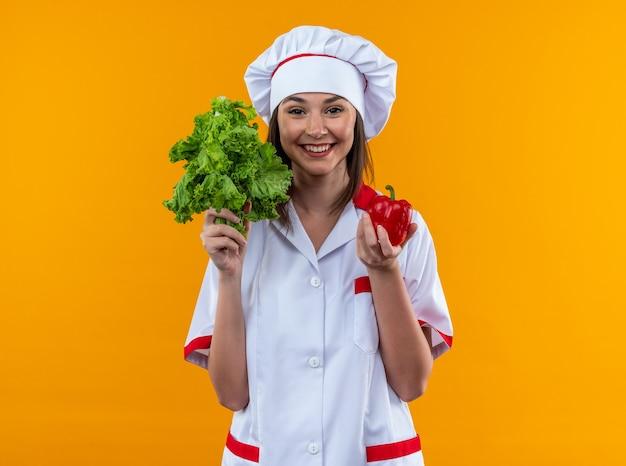 Uśmiechnięta młoda kucharka w mundurze szefa kuchni trzymająca sałatkę z pieprzem odizolowana na pomarańczowej ścianie