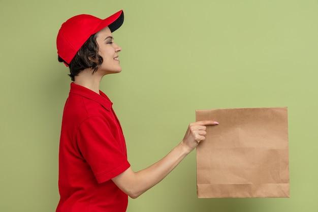 Uśmiechnięta młoda ładna dostawa kobieta stojąca bokiem trzymająca papierowe opakowanie żywności
