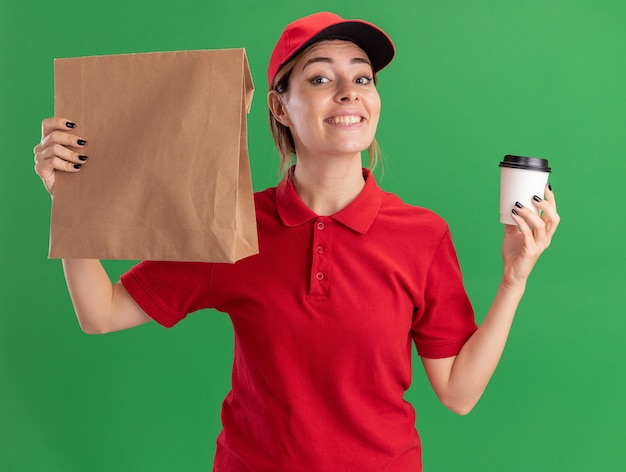 Uśmiechnięta młoda ładna dostawa kobieta w mundurze trzyma papierowy kubek i pakiet papieru na białym tle na zielonej ścianie