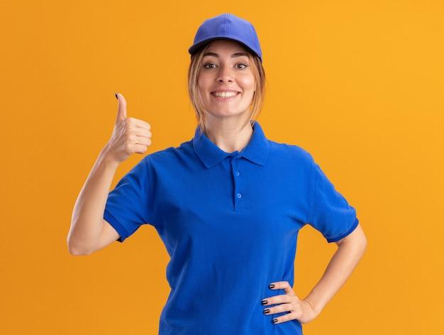 Uśmiechnięta młoda ładna dziewczyna dostawy w mundurze kciuki do góry patrząc na kamery na pomarańczowo