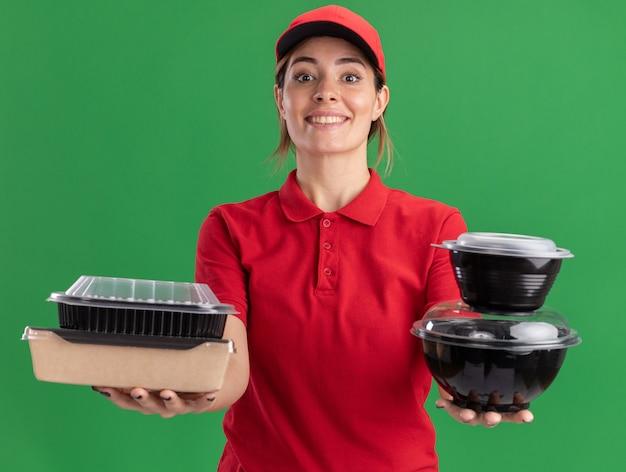 Uśmiechnięta młoda ładna dziewczyna dostawy w mundurze posiada pojemniki na żywność na zielono