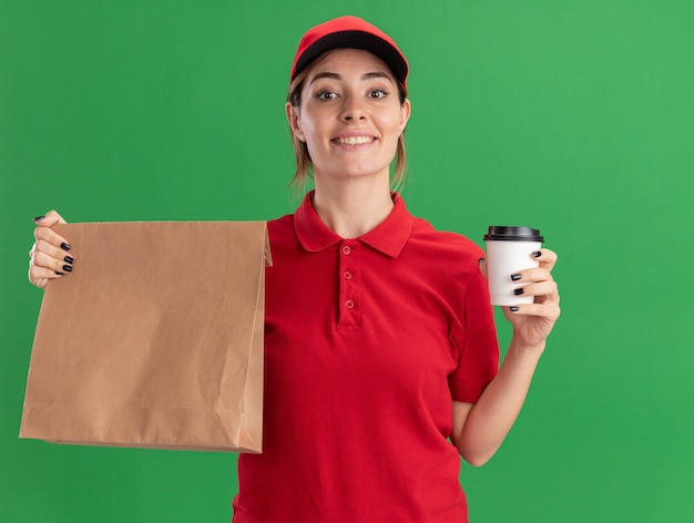 Uśmiechnięta młoda ładna dziewczyna dostawy w mundurze trzyma pakiet papieru i papierowy kubek na zielono