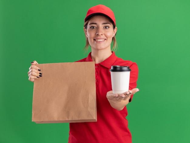 Uśmiechnięta młoda ładna dziewczyna dostawy w mundurze trzymając pakiet papieru i papierowy kubek na zielono