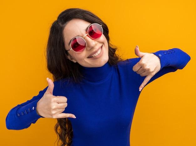 Uśmiechnięta młoda ładna dziewczyna nosi okulary przeciwsłoneczne, patrząc na kamerę, wykonując luźny gest