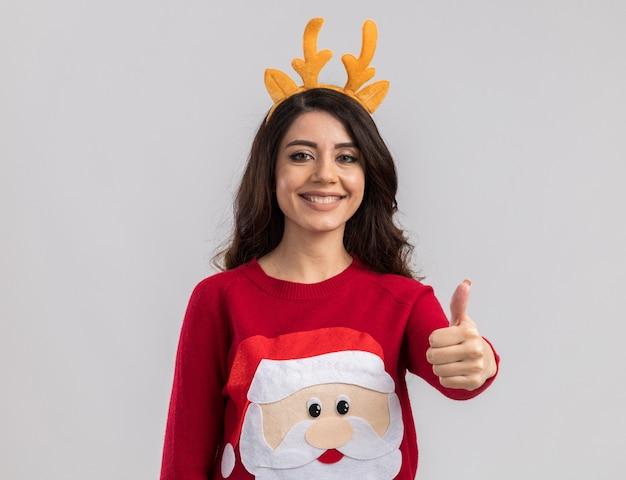 Uśmiechnięta młoda ładna dziewczyna nosi pałąk poroża renifera i sweter świętego mikołaja patrząc pokazując kciuk do góry