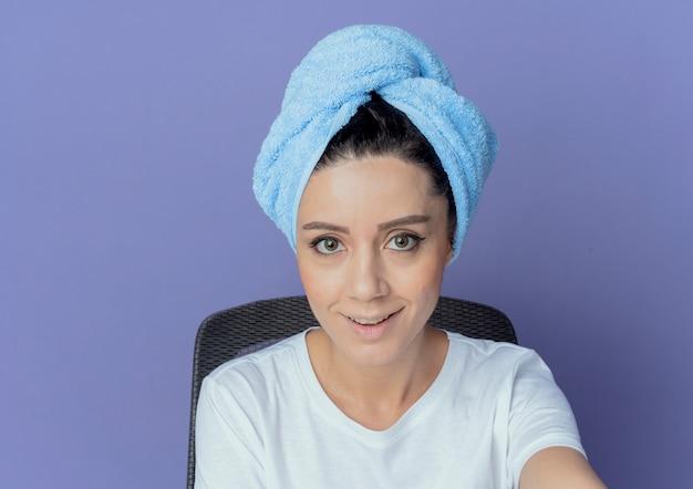 Uśmiechnięta młoda ładna dziewczyna siedzi przy stole do makijażu z narzędziami do makijażu iz ręcznikiem na głowie patrząc na kamery na białym tle na fioletowym tle