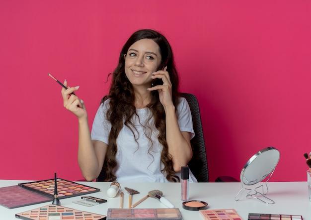 Uśmiechnięta młoda ładna dziewczyna siedzi przy stole do makijażu z narzędziami do makijażu, rozmawia przez telefon i trzyma pędzel do cieni do powiek, patrząc na bok odizolowany na szkarłatnym tle