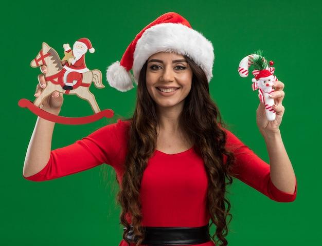 Uśmiechnięta młoda ładna dziewczyna ubrana w santa hat trzyma santa na koniu na biegunach figurka i ozdoba trzciny cukrowej patrząc na kamery na białym tle na zielonym tle