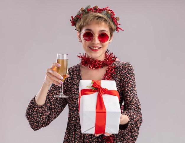 Uśmiechnięta młoda ładna dziewczyna ubrana w świąteczny wieniec i blichtrową girlandę na szyi w okularach trzymających pakiet prezentów i kieliszek szampana na białej ścianie z miejscem na kopię