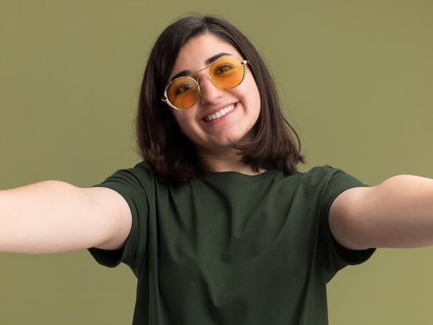 Uśmiechnięta młoda ładna dziewczynka kaukaski w okularach przeciwsłonecznych udaje, że trzyma aparat przy selfie na oliwkowej zieleni