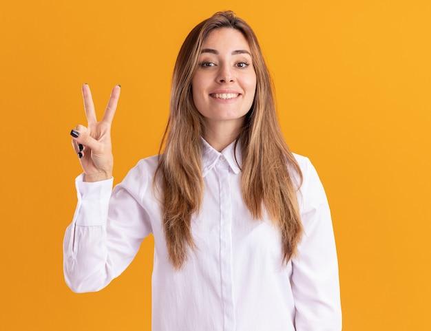 Uśmiechnięta młoda ładna kaukaska dziewczyna gestykuluje znak zwycięstwa na pomarańczowej ścianie z miejscem na kopię
