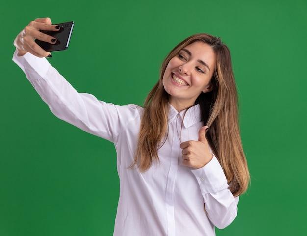Uśmiechnięta młoda ładna kaukaska dziewczyna kciuki w górę, trzymająca i patrząca na telefon, biorąc selfie