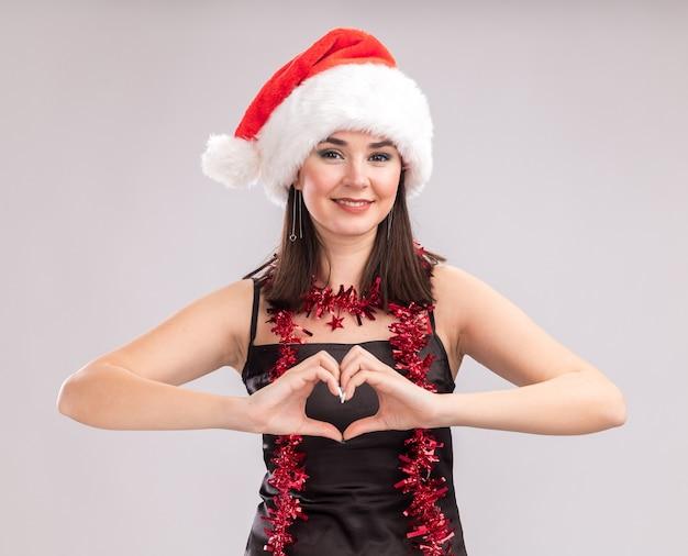 Uśmiechnięta młoda ładna kaukaska dziewczyna nosi santa hat i blichtr girlanda wokół szyi patrząc na kamery robi znak serca na białym tle