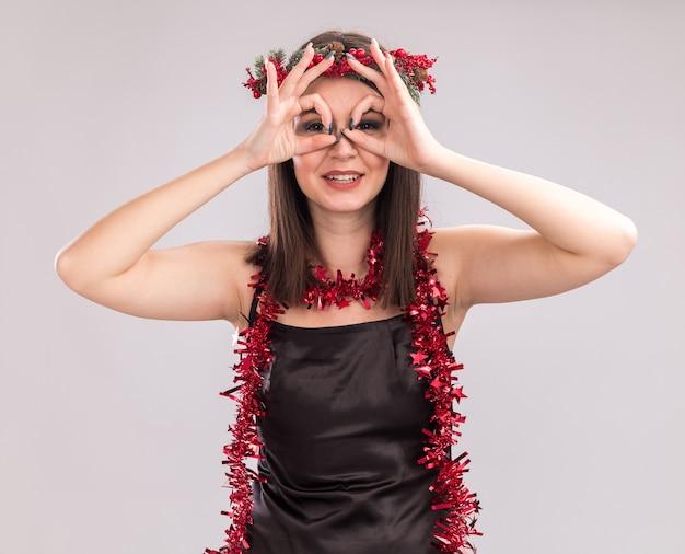 Uśmiechnięta młoda ładna kaukaska dziewczyna nosi świąteczny wieniec głowy i blichtr wianek wokół szyi patrząc na kamery robi gest spojrzenia za pomocą rąk jako lornetki na białym tle