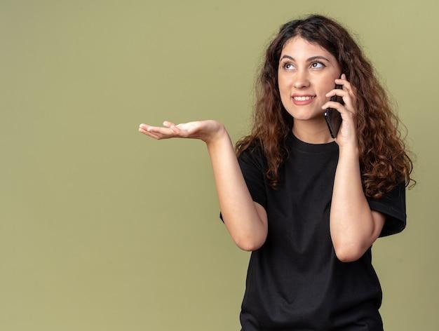 Uśmiechnięta młoda ładna kaukaska dziewczyna rozmawia przez telefon, patrząc w górę pokazując pustą rękę odizolowaną na oliwkowozielonej ścianie z kopią miejsca