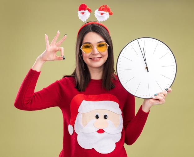 Uśmiechnięta młoda ładna kaukaska dziewczyna ubrana w sweter świętego mikołaja i opaskę w okularach trzyma zegar patrząc na kamerę, robi znak ok na białym tle na oliwkowym tle