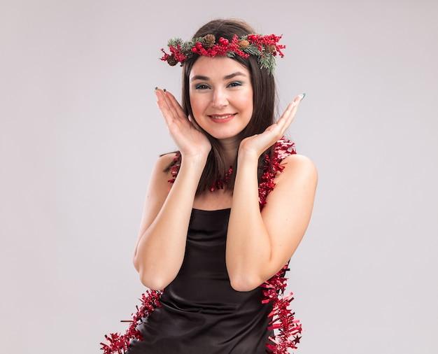 Uśmiechnięta młoda ładna kaukaska dziewczyna ubrana w świąteczny wieniec i blichtrową girlandę wokół szyi, patrząc na kamerę trzymającą ręce w pobliżu głowy na białym tle z kopią przestrzeni