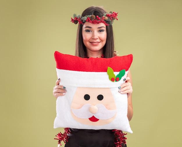 Uśmiechnięta młoda ładna kaukaska dziewczyna ubrana w świąteczny wieniec z głowy i blichtrową girlandę na szyi trzymającą poduszkę świętego mikołaja patrząc na kamerę odizolowaną na oliwkowozielonym tle z kopią przestrzeni