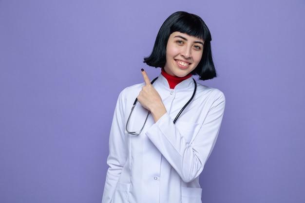Uśmiechnięta młoda ładna kaukaska dziewczyna w mundurze lekarza ze stetoskopem skierowanym w górę
