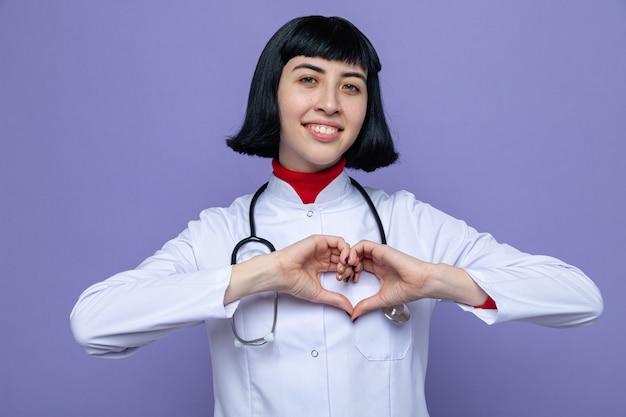 Uśmiechnięta młoda ładna kaukaska dziewczyna w mundurze lekarza ze stetoskopem wskazującym znak serca