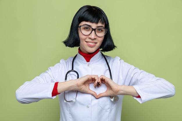 Uśmiechnięta młoda ładna kaukaska dziewczyna w okularach optycznych w mundurze lekarza ze stetoskopem wskazującym znak serca
