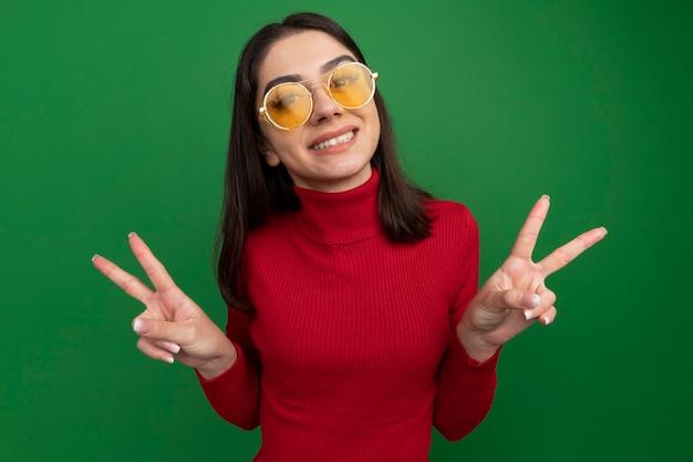 Uśmiechnięta młoda ładna kaukaska dziewczyna w okularach przeciwsłonecznych robi znak pokoju na zielonej ścianie