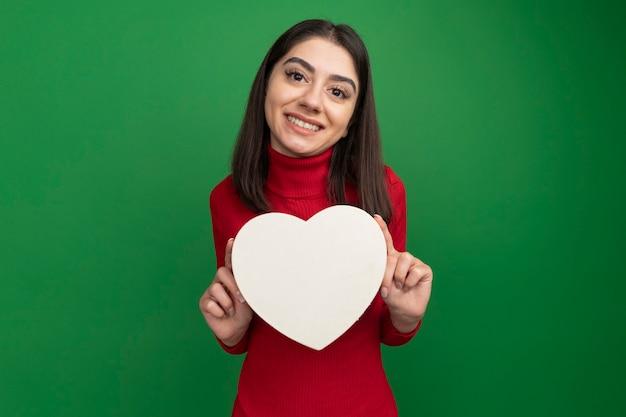Uśmiechnięta młoda ładna kaukaska kobieta trzyma kształt serca