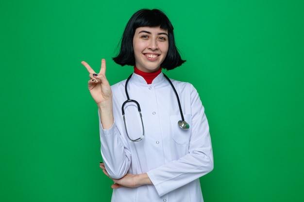 Uśmiechnięta młoda ładna kaukaska kobieta w mundurze lekarza ze stetoskopem wskazującym znak zwycięstwa