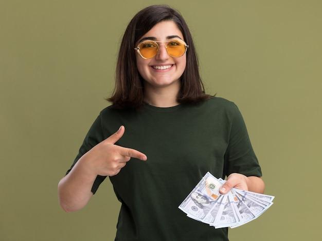 Uśmiechnięta młoda ładna kaukaski dziewczyna w okularach przeciwsłonecznych, trzymając i wskazując na pieniądze na oliwkowej zieleni