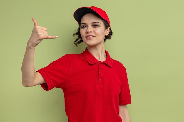 Uśmiechnięta młoda ładna kobieta dostawy gestem powiesić luźny znak