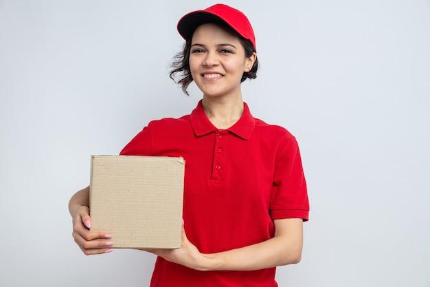Uśmiechnięta młoda ładna kobieta dostawy trzymająca karton