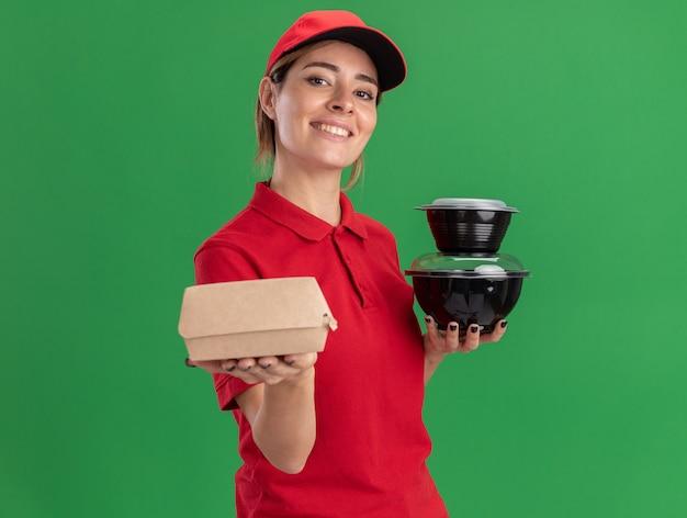 Uśmiechnięta młoda ładna kobieta dostawy w mundurze gospodarstwa pojemniki na żywność i pakiet żywności na białym tle