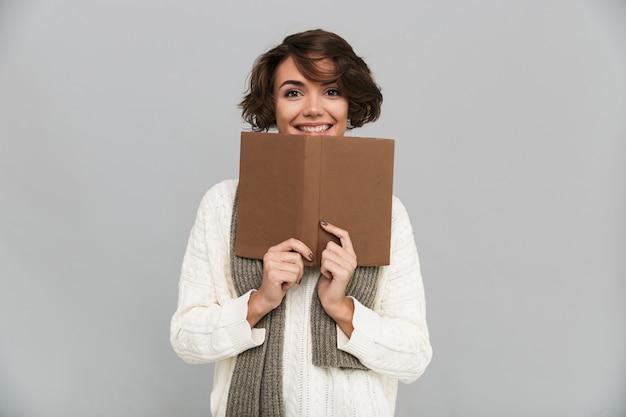 Uśmiechnięta młoda ładna kobieta jest ubranym szalika czytelniczą książkę.