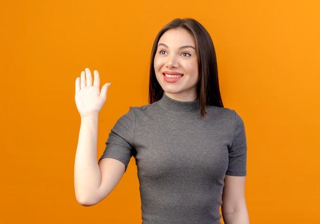 Uśmiechnięta młoda ładna kobieta, patrząc na bok i gestykuluje cześć na białym tle na pomarańczowym tle