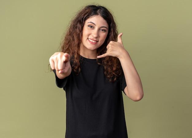 Uśmiechnięta młoda ładna kobieta, patrząca i wskazująca z przodu, wykonująca gest połączenia odizolowana na oliwkowozielonej ścianie z miejscem na kopię copy