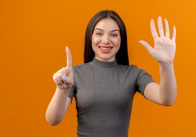 Uśmiechnięta młoda ładna kobieta pokazuje jeden i pięć z rękami na białym tle na pomarańczowym tle