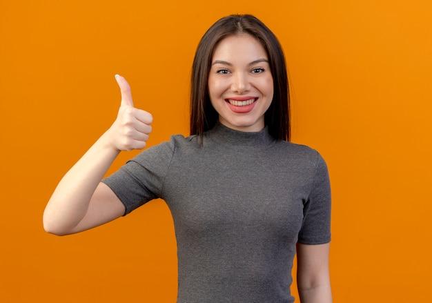 Uśmiechnięta młoda ładna kobieta pokazuje kciuk na białym tle na pomarańczowym tle