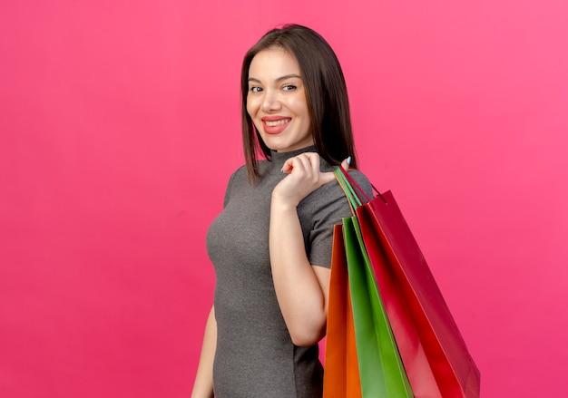 Uśmiechnięta młoda ładna kobieta, stojąca w widoku profilu, trzymając torby na zakupy na ramieniu na białym tle na różowym tle z miejsca na kopię