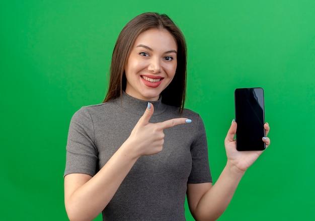 Uśmiechnięta młoda ładna kobieta trzyma i wskazuje na telefon komórkowy na białym tle na zielonym tle