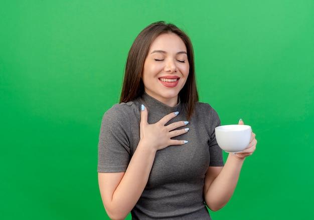 Uśmiechnięta młoda ładna kobieta trzyma kubek kładąc rękę na klatce piersiowej z zamkniętymi oczami na białym tle na zielonym tle z miejsca na kopię