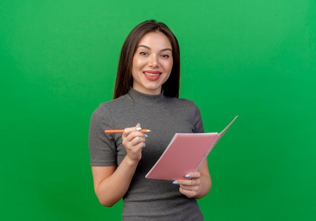 Uśmiechnięta młoda ładna kobieta trzymając notes i długopis samodzielnie na zielono z miejsca na kopię