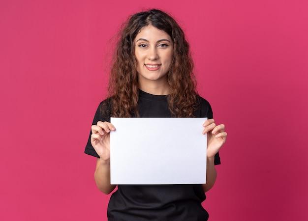 Uśmiechnięta młoda ładna kobieta trzymająca czysty papier