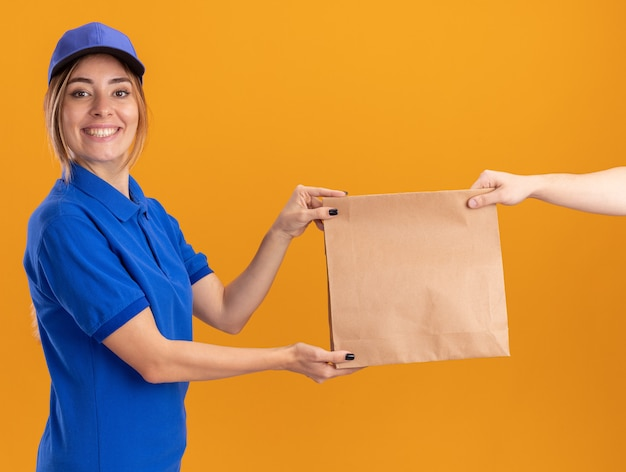 Uśmiechnięta młoda ładna kobieta w mundurze dostawy daje pakiet papieru do kogoś, kto szuka na białym tle