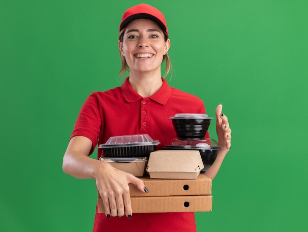 Uśmiechnięta młoda ładna kobieta w mundurze trzyma papierowe opakowania żywności i pojemniki na pudełkach po pizzy na białym tle na zielonej ścianie