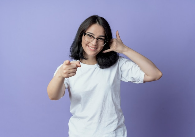 Uśmiechnięta młoda ładna kobieta w okularach robi gest połączenia i wskazując na przód