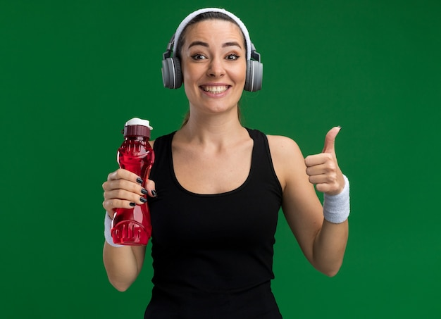 Uśmiechnięta młoda ładna sportowa kobieta nosi opaskę i opaski ze słuchawkami, trzymając butelkę wody, patrząc na przód pokazując kciuk na białym tle na zielonej ścianie