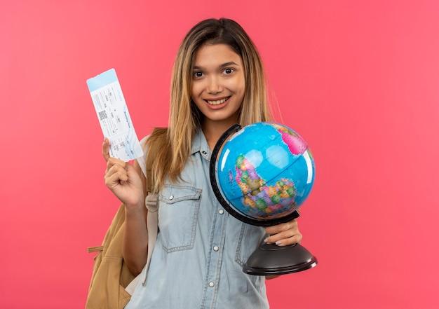 Uśmiechnięta młoda ładna studencka dziewczyna ubrana w torbę z powrotem trzymając bilet lotniczy i kula ziemska na białym tle na różowej ścianie