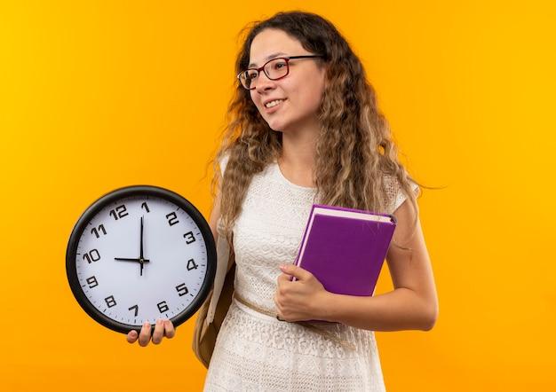 Uśmiechnięta młoda ładna uczennica w okularach i plecak trzyma zegar i książkę patrząc na bok na białym tle na żółtej ścianie