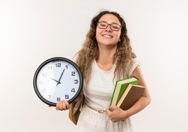 Uśmiechnięta młoda ładna uczennica w okularach i plecak trzymając książki i zegar na białym tle na białej ścianie