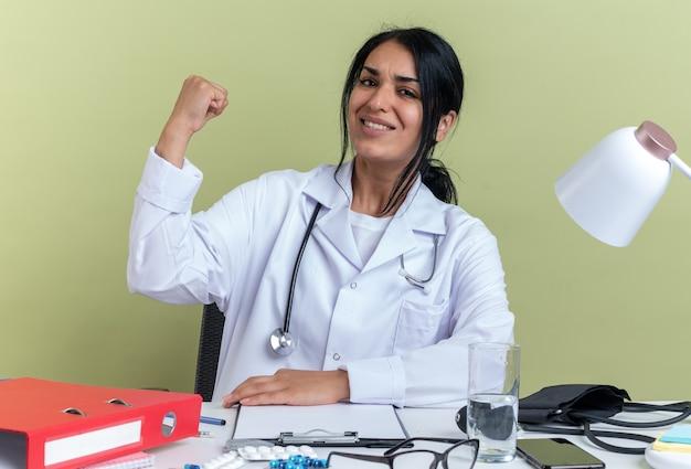 Uśmiechnięta młoda lekarka ubrana w szatę medyczną ze stetoskopem siedzi przy biurku z narzędziami medycznymi pokazującymi gest tak na białym tle oliwkowo-zielonym